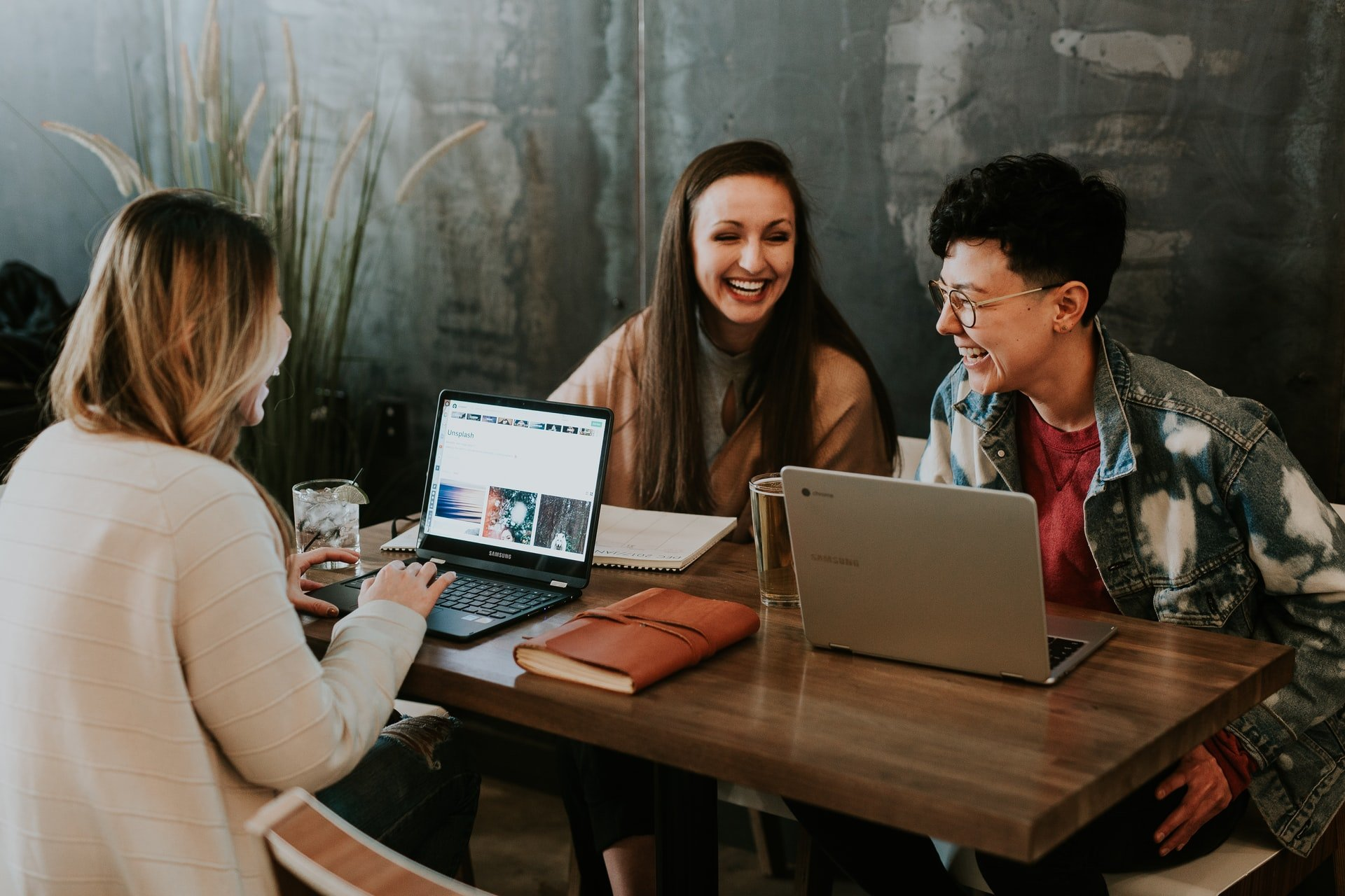 Tre unga kvinnor sitter vid ett bord med sina datorer, de pratar och skrattar